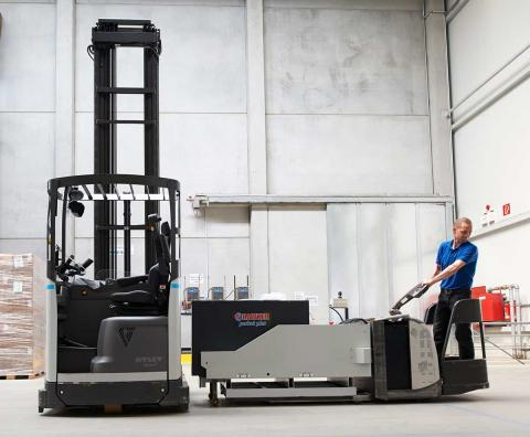 A Centrotherm employee changes the battery on a UniCarriers reach truck