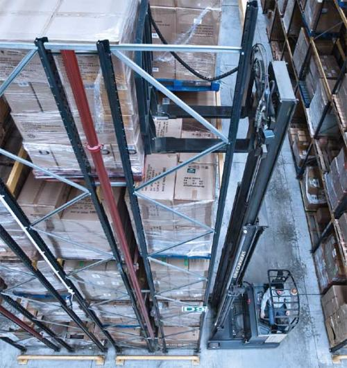 A UniCarriers reach truck with telescopic forks extracts a pallet from double deep racking